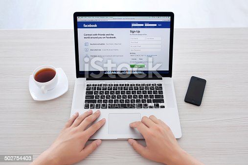 588359078 istock photo man sitting at the MacBook retina with site Facebook 502754403