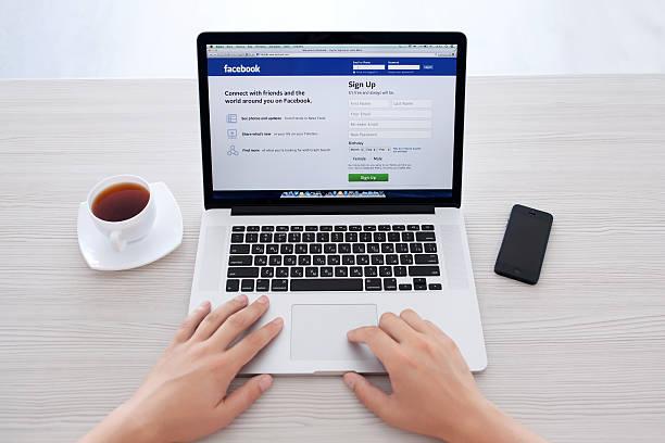 mann, sitzend auf der netzhaut macbook mit website facebook - www kaffee oder tee stock-fotos und bilder
