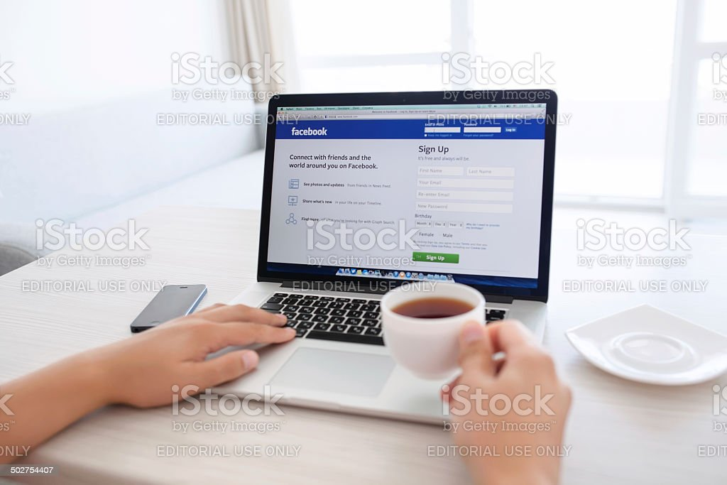 man sitting at the MacBook retina with site Facebook royalty-free stock photo