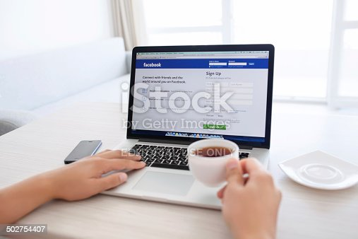 588359078 istock photo man sitting at the MacBook retina with site Facebook 502754407