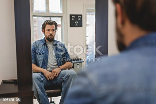 698023272 istock photo Man sitting at the modern barber shop 996128136