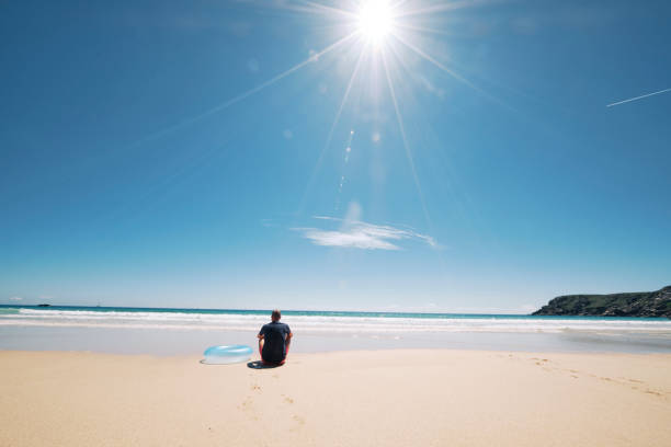 man sitting at the shoreline of the idyllic pedn vounder beach, cornwall on a hot sunny june day. - rubber ring stock photos and pictures
