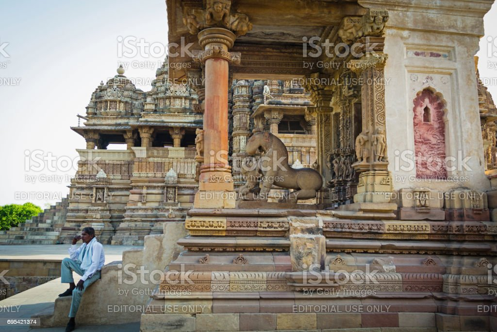 A man sitting at the stairs of Mahadeva Temple in the Western Group of Temples in the late afternoon stock photo