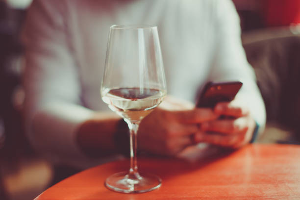 Man sitting at the table with a glass of white sparkling wine and mobile phone  - focus on glass