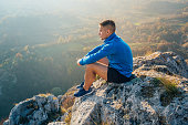 Young caucasian man sitting at the top of mountain and looking at view