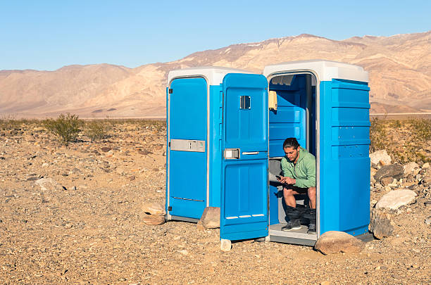 man sitting at toilet in the middle of death valley - cell phone toilet stockfoto's en -beelden