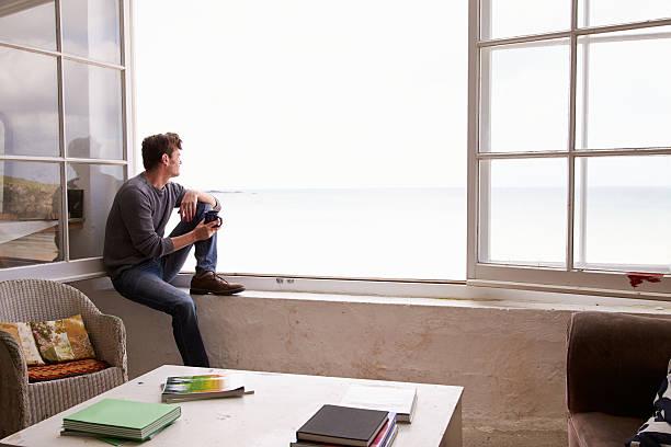 Mann sitzt am Fenster und Blick auf die wunderschönen Blick auf den Strand – Foto