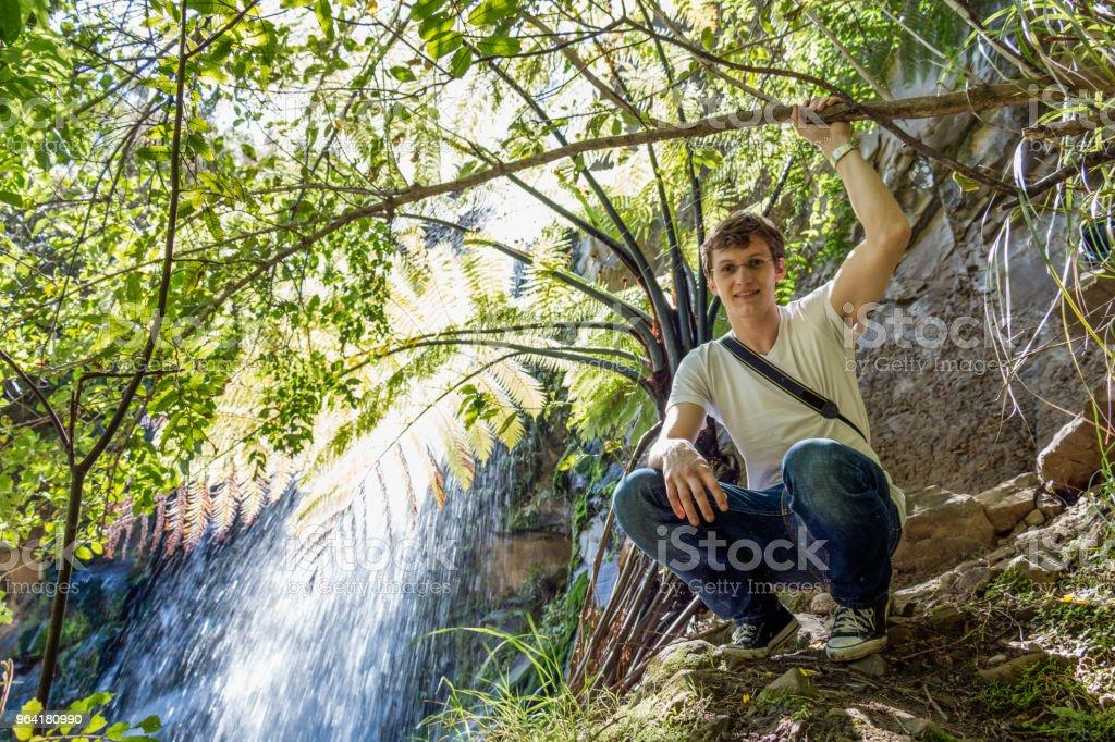 Homem sentado por uma cachoeira - foto de acervo