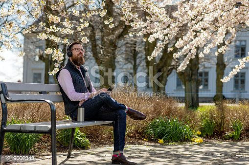 A man is sitting on a bench by cherry blossom trees. He is wearing headphones and is holding a smartphone. There is a reusable travel mug next to him.