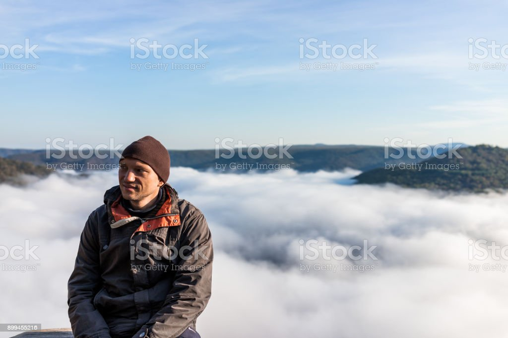Man sitting by mountains and fog clouds covering valley in morning sunrise in Grandview Overlook, West Virginia smiling happy stock photo