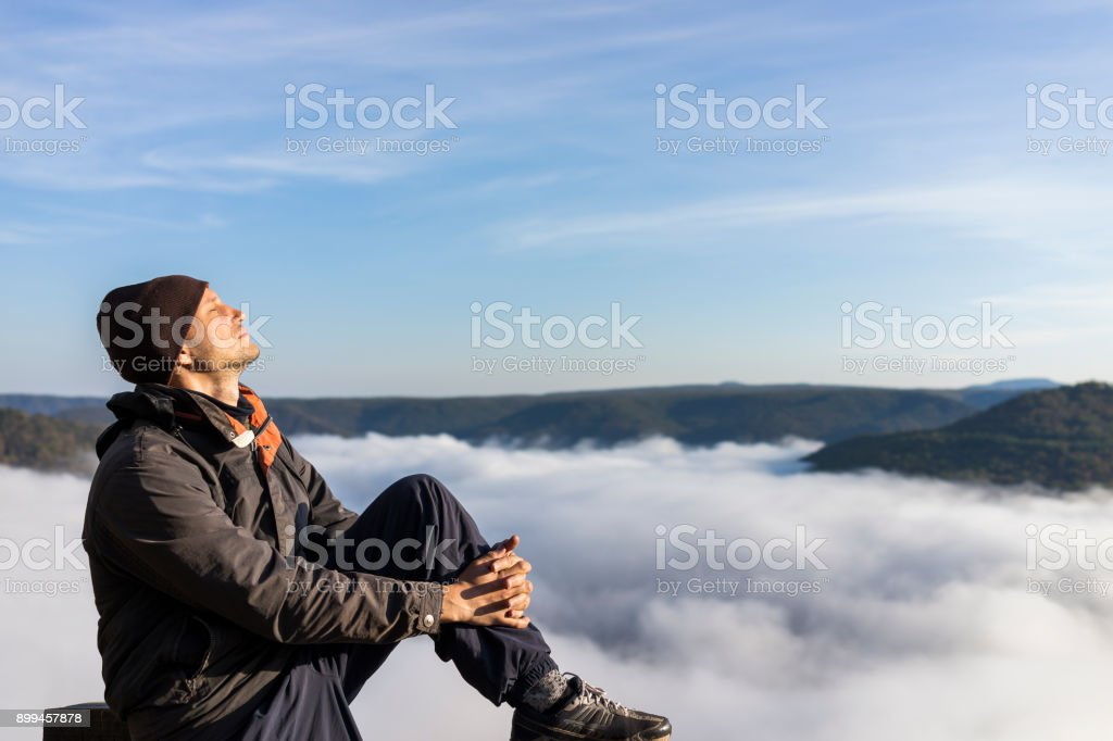 Man sitting by mountains and fog clouds covering valley in morning sunrise in Grandview Overlook, West Virginia stock photo