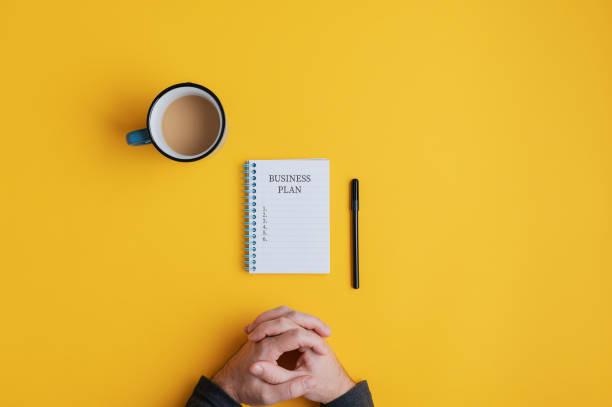 Mann sitzt an Spiral-Notebook mit Business-Plan-Ideen bereit, in sie geschrieben werden – Foto