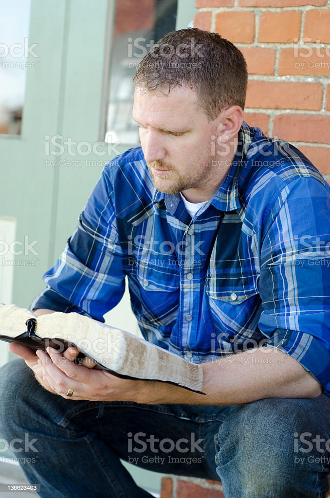 man sitting down reading the bible stock photo