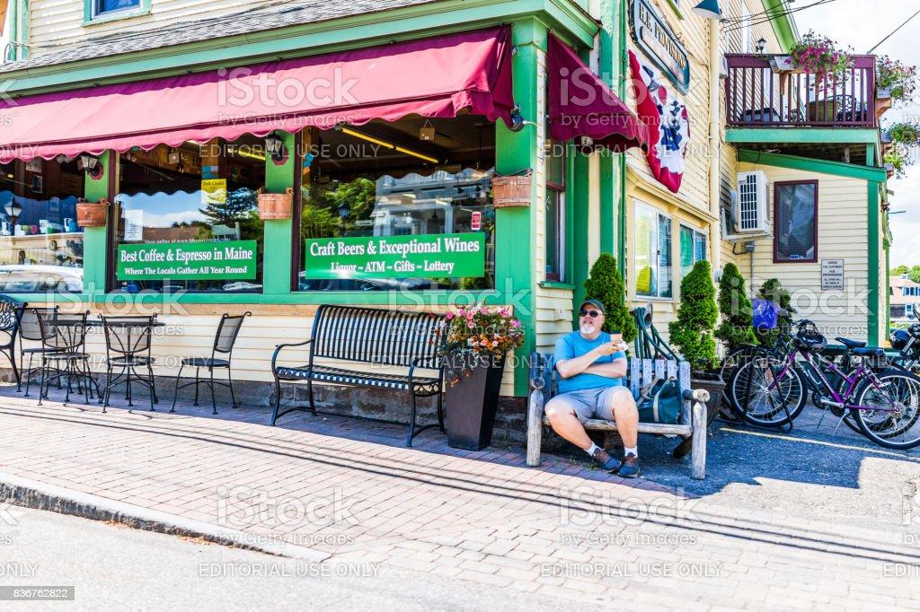 Man sitting drinking coffee by restaurant on sidewalk street in downtown village during summer day stock photo