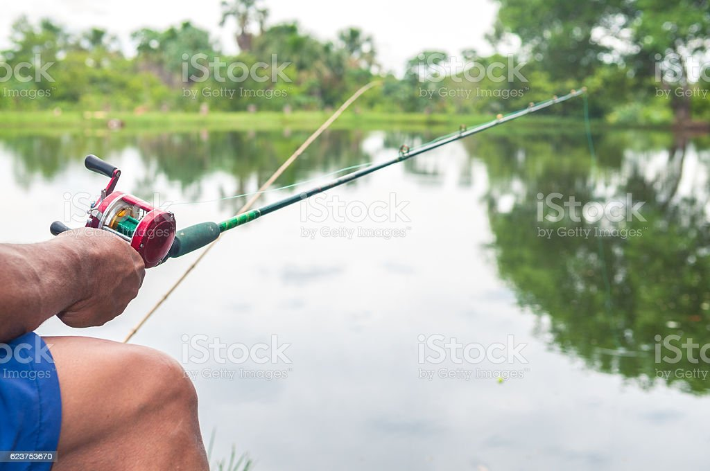 Man sitting holding a fishing rod. Fishing on lake. - foto de acervo