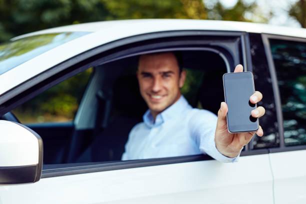 Un hombre sentado en un coche muestra un teléfono móvil - foto de stock