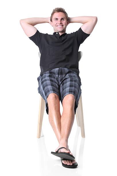 uomo seduto in una sedia e sorridente - mani dietro la testa foto e immagini stock