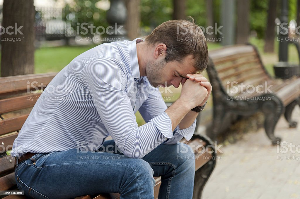 Man sitting in a public garden on a bench with his head down stock photo