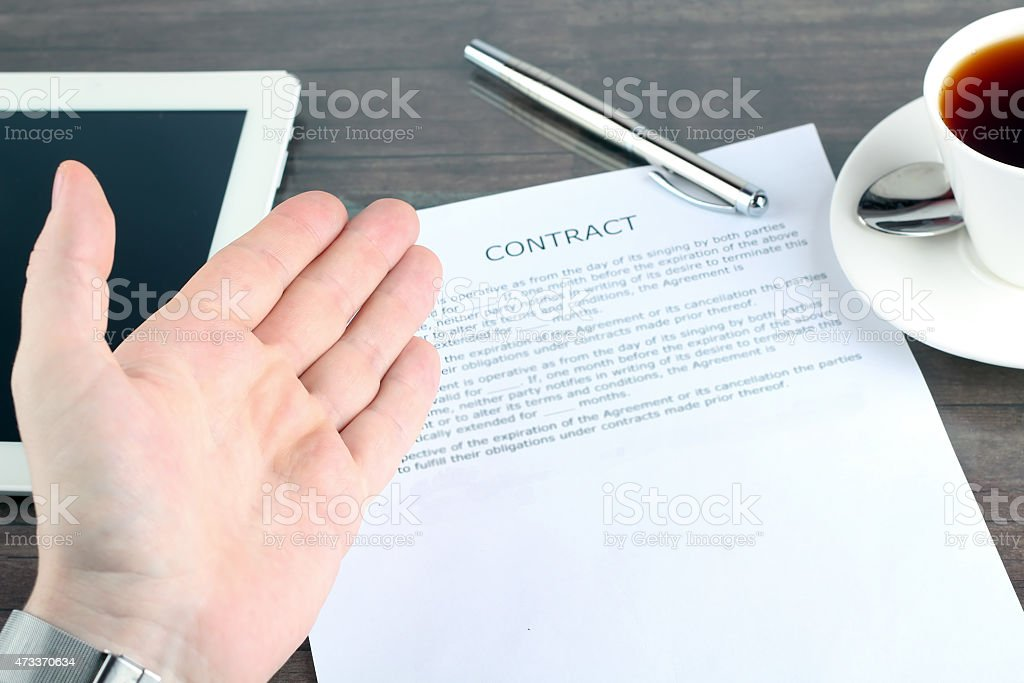 Man sitting in a table showing, offering  a contract stock photo