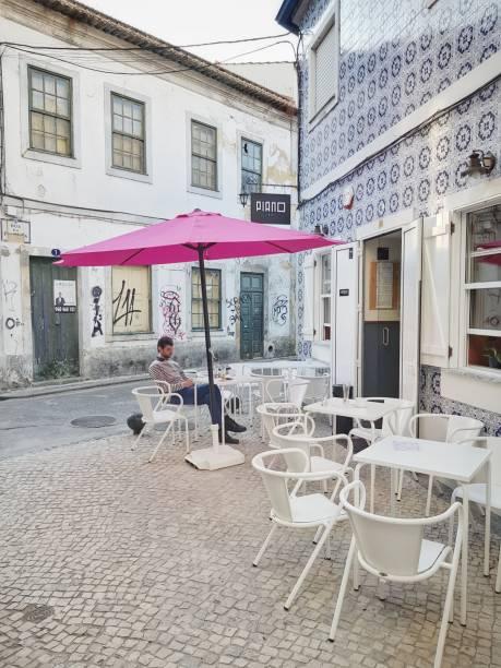 man sitting in a terrace having a coffee in a street of aveiro - esplanada portugal imagens e fotografias de stock