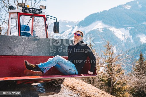 Saalbach, Austria - March 20, 2018: Young man sitting in a trunk of a tractor watching beautiful mountains in the Alps