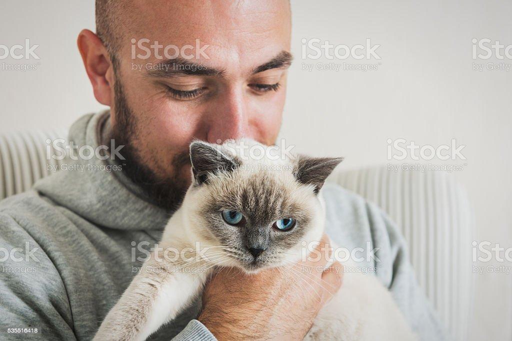 Mann sitzt auf Sessel halten seine wunderschönen Haustier Katze – Foto