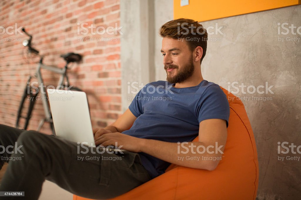 Man sitting in bean bag and using laptop. stock photo