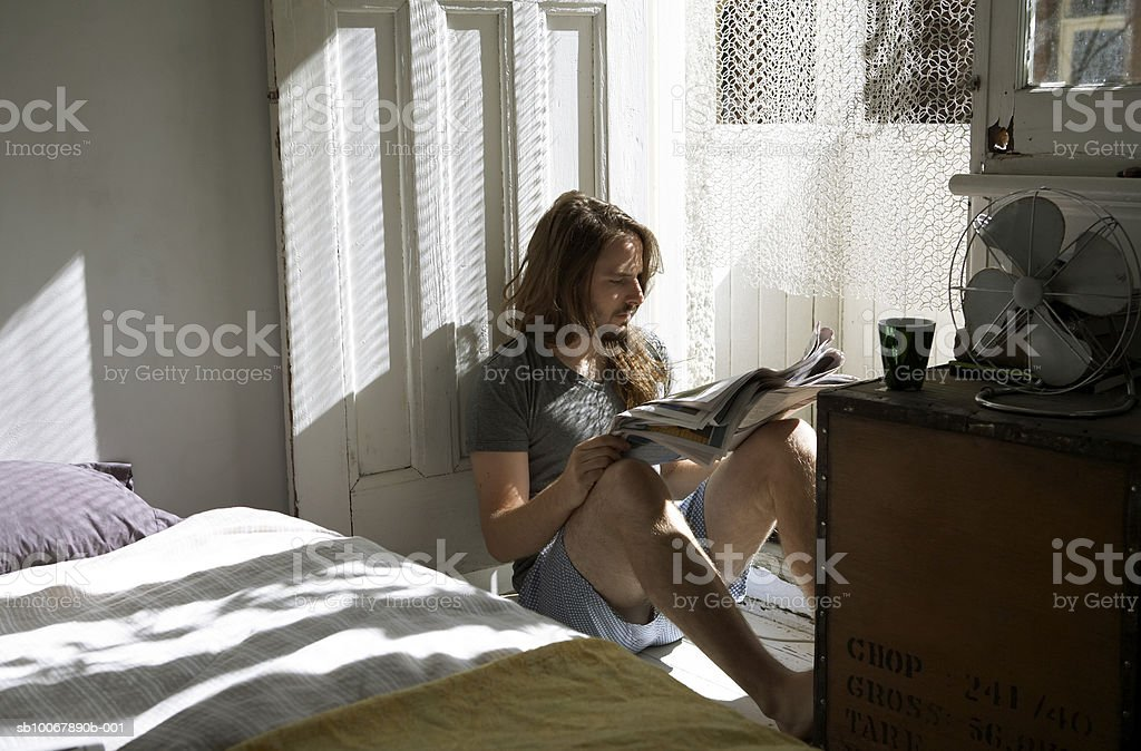 Man sitting in bedroom, reading newspaper royalty-free stock photo