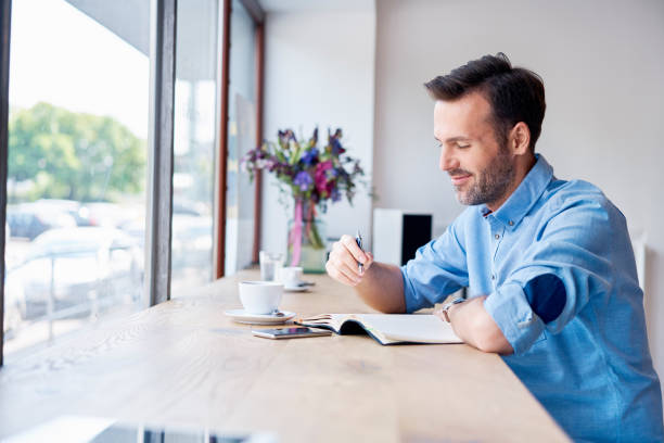 Man sitting in cafe drinking coffee and writing in personal calendar Man sitting in cafe drinking coffee and writing in personal calendar illustrator stock pictures, royalty-free photos & images