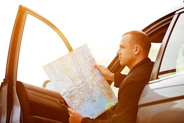 Mann sitzend im Auto und lesen Karte – Foto