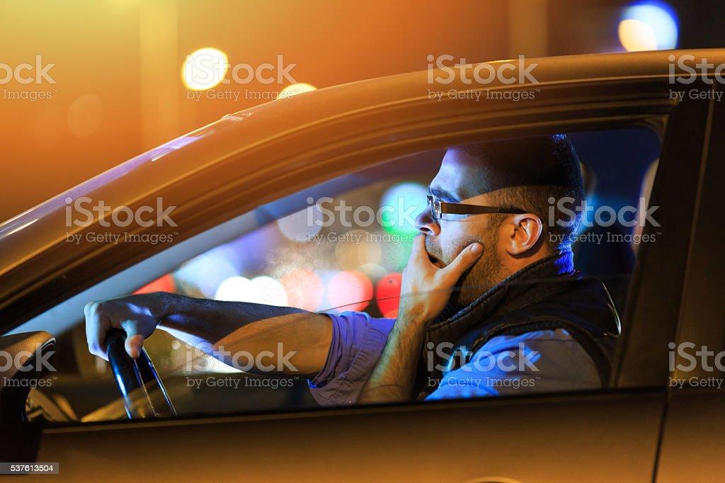 Mann sitzend im Auto und Gähnen bei Nacht Lizenzfreies stock-foto