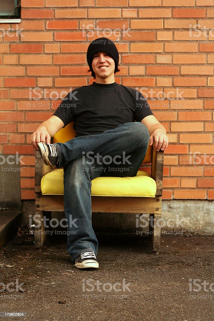 Man sitting in chair outside smiling with leg crossed royalty-free stock photo