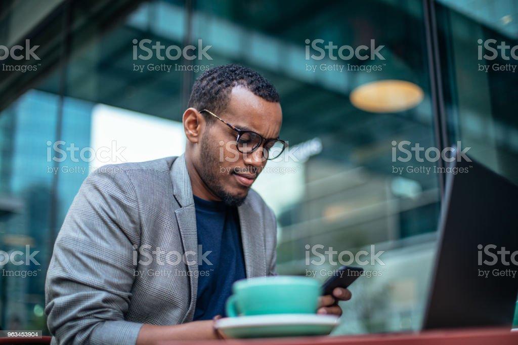 Man sitting in coffee shop and texting - Zbiór zdjęć royalty-free (Afrykanin)