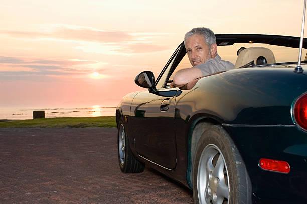 mann sitzt im cabrio auf die küste - 1m coupe stock-fotos und bilder
