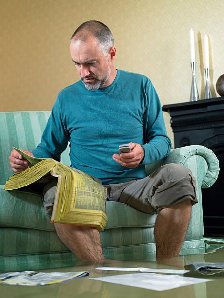 Mann sitzt in der lichtdurchfluteten Wohnzimmer mit Telefon – Foto