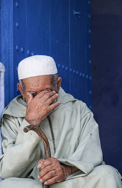 man sitting in front of a blue door in Morocco. – zdjęcie