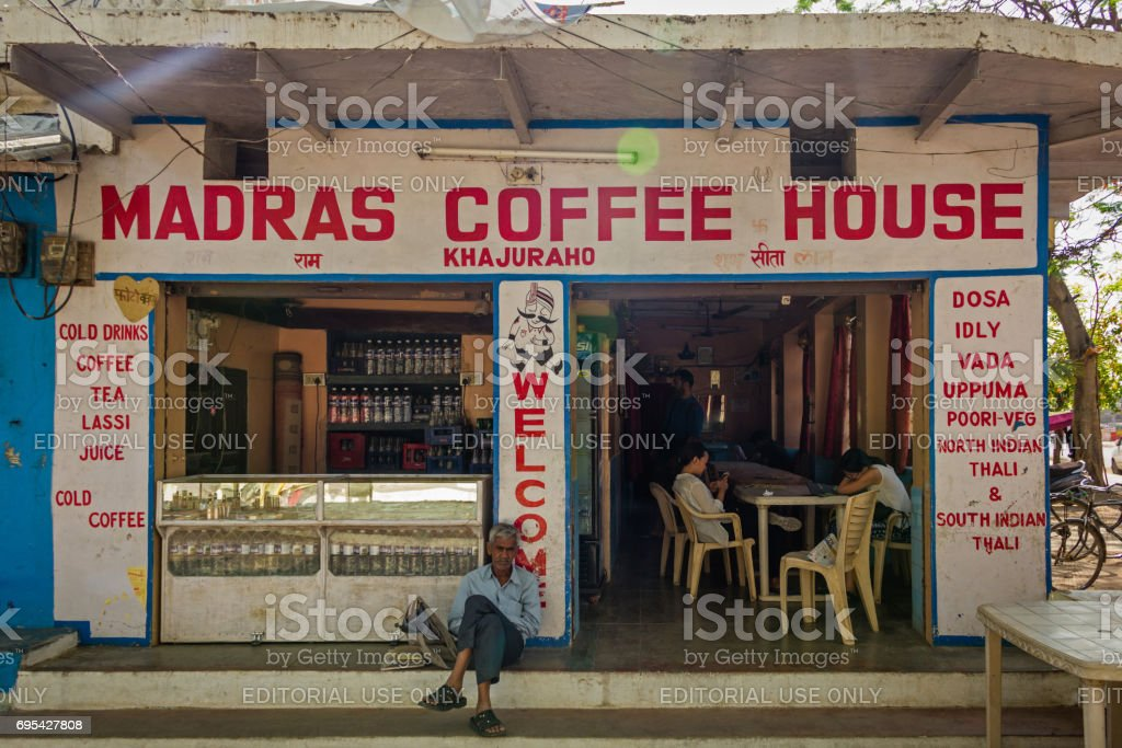 A man sitting in front of Madras Coffee House stock photo