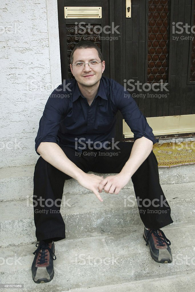 Man sitting in front of the house stock photo