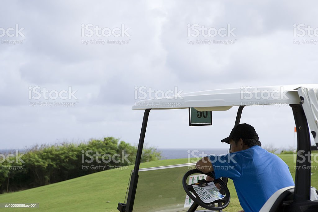 Man sitting in golf cart looking away royalty-free stock photo