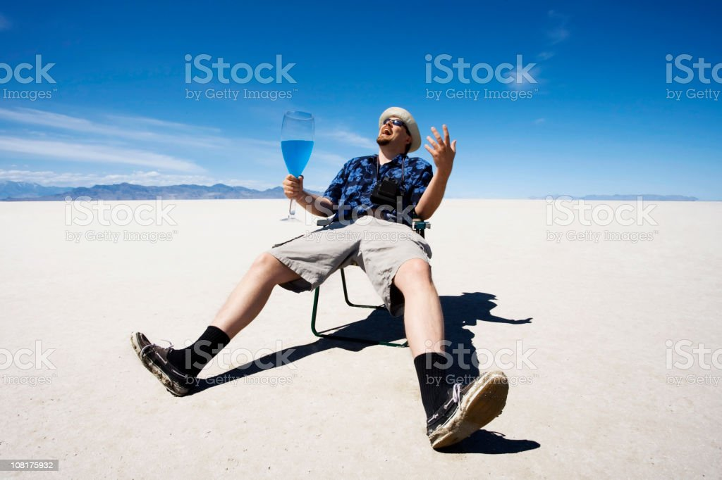 Man Sitting in Lawn Chair and Drinking at Salt Flats royalty-free stock photo