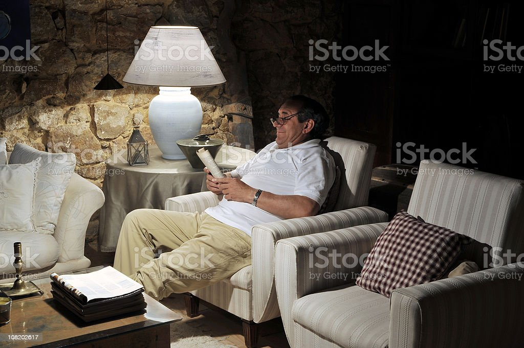 Man Sitting in Living Room and Reading Book royalty-free stock photo
