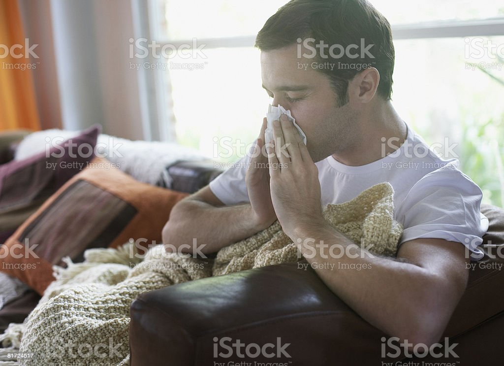 Man sitting in living room blowing nose stock photo
