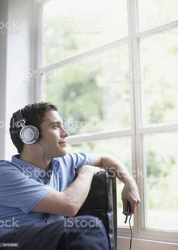 Man sitting in living room listening to MP3 player royalty-free stock photo