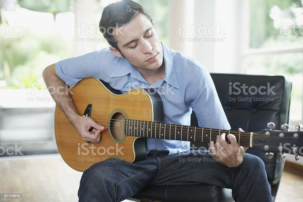 Man sitting in living room playing acoustic guitar stock photo