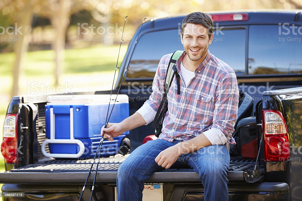 Man Sitting In Pick Up Truck On Camping Holiday stock photo