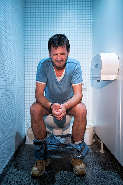 man sitting in public restroom stock photo