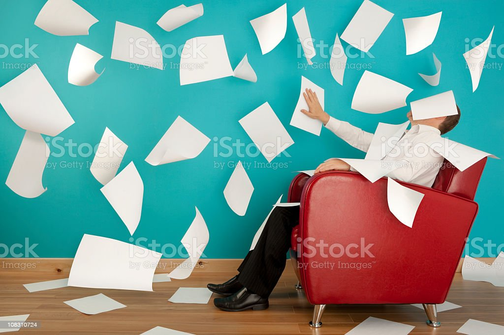 Man sitting in red chair with papers flying all around him stock photo