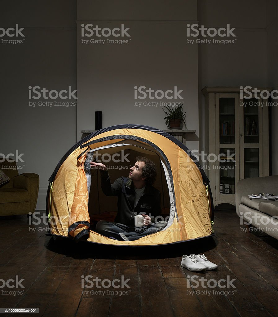 Man sitting in tent in living room royalty-free stock photo
