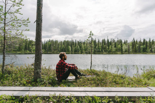 Man sitting in the forest near the river stock photo
