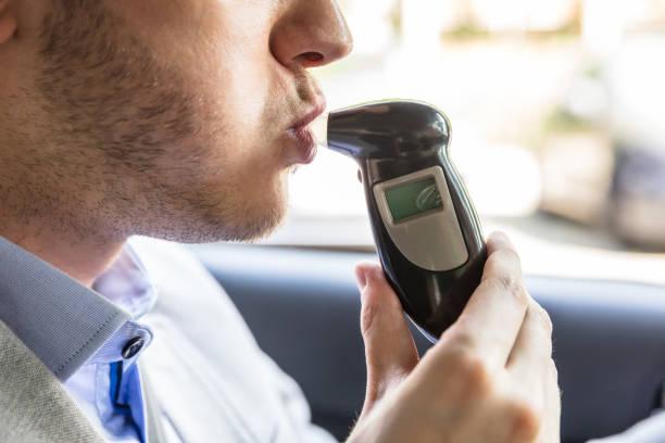 Homem sentado dentro do carro a fazer teste de álcool - foto de acervo
